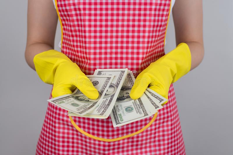 Work good and be paid good concept. Cropped closeup photo of hand in bright gloves holding checking amount pile on money isolated. Grey background royalty free stock photo