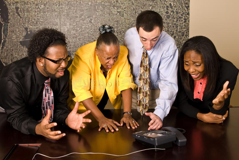 Work group on a conference call. A group of workers stand at a a conference room table during a conference call. All four team members gesture toward the phone royalty free stock photography