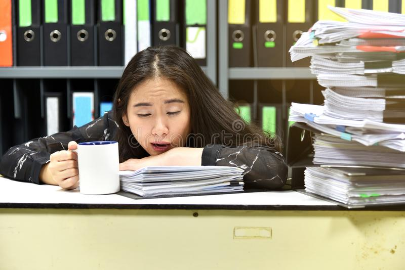 Work hard, Lot of work, Stacks of document paper and files folder on office desk. Sleepy officer yawning while holding coffee cup at workplace stock photography