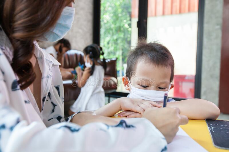 Work from home. Mother teaching and playing with her son while they quarantine for Coronavirus COVID-19. Mother and son wearing protective mask while working royalty free stock photo