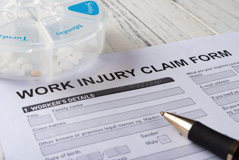 Work injury claim form with box of pills and a pen medical & insurance concept. Work injury claim form with box of pills and a pen medical and insurance concept royalty free stock images