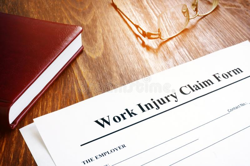 Work injury claim form and glasses on desk. Work injury claim form and glasses on the desk royalty free stock photography