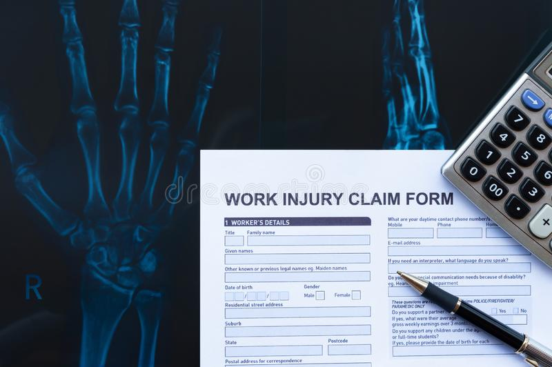 Work injury claim form with pen & calculator on top of an X-ray film medical and insurance concept. Work injury claim form with pen and calculator on top of an X royalty free stock photos