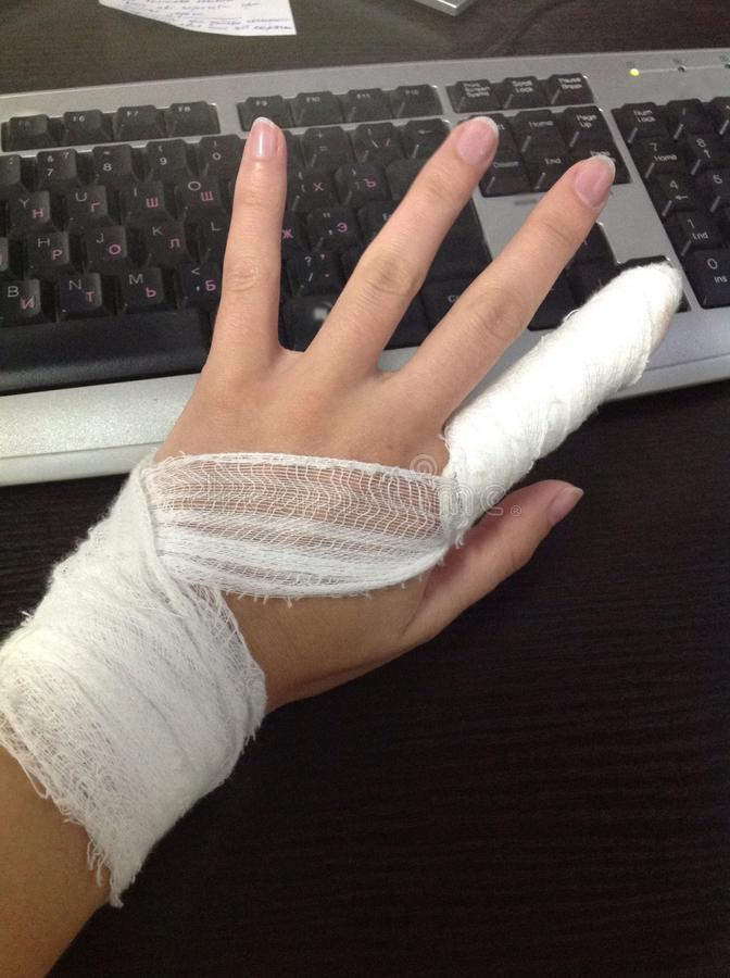 Work injury. Female hand with a bandaged finger on the background of a dark table and black keyboard royalty free stock image