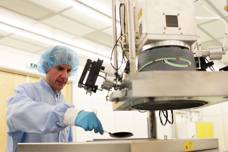 At work inside a high tech cleanroom. At work inside a high tech clean room on a atomic layer deposition machine stock photography