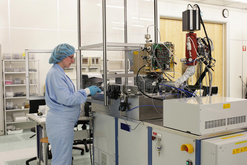 At work inside a high tech cleanroom. A pregnant woman at work inside a high tech clean room on a atomic layer deposition machine royalty free stock image