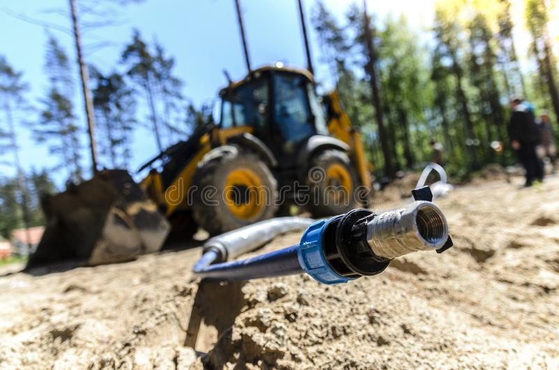 The work of a large two-wheeled tractor when laying water supply for water supply of private homes. royalty free stock images