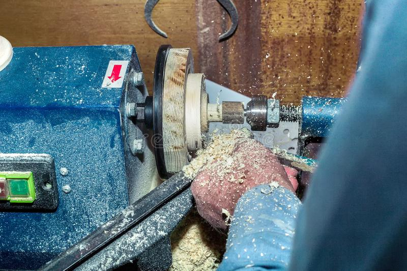 Work on a lathe on a tree. Close-up of male hands during the processing of wooden blanks.  stock photo