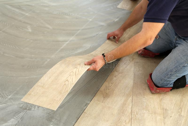 Work on laying flooring. Worker installing new vinyl tile floor. stock photo
