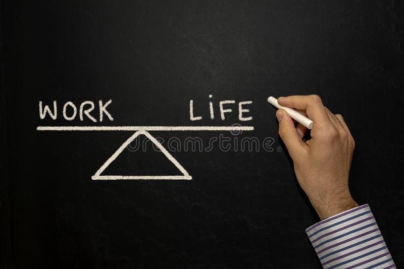 Work life balance. Balance showing work and life on a blackboard stock images