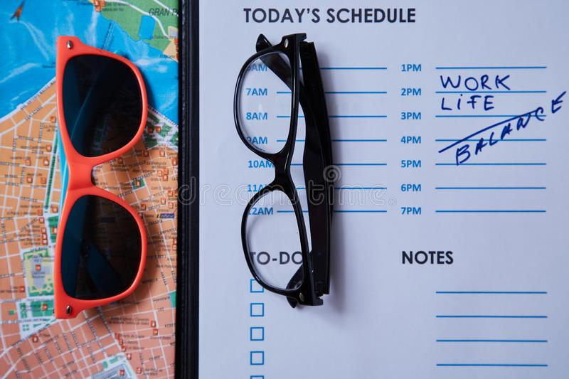 Work life balance choice concept: colored sunglasses and strict office glasses.  royalty free stock photography