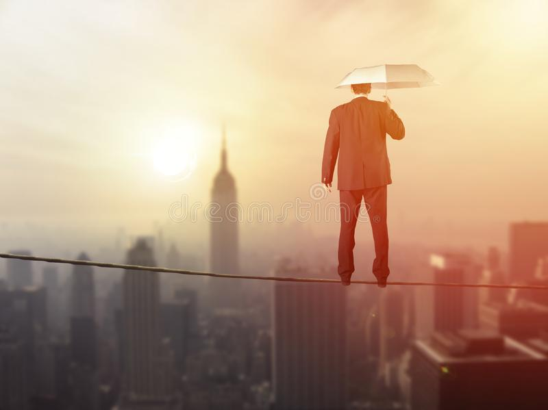 Work life balance concept: Business man balancing above the city royalty free stock image