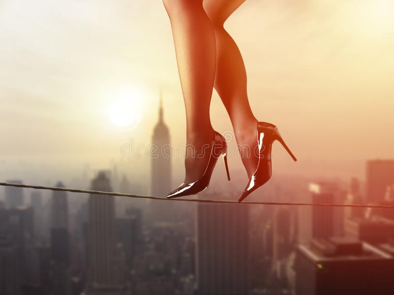 Work life balance concept: Business woman balancing above the city royalty free stock photography