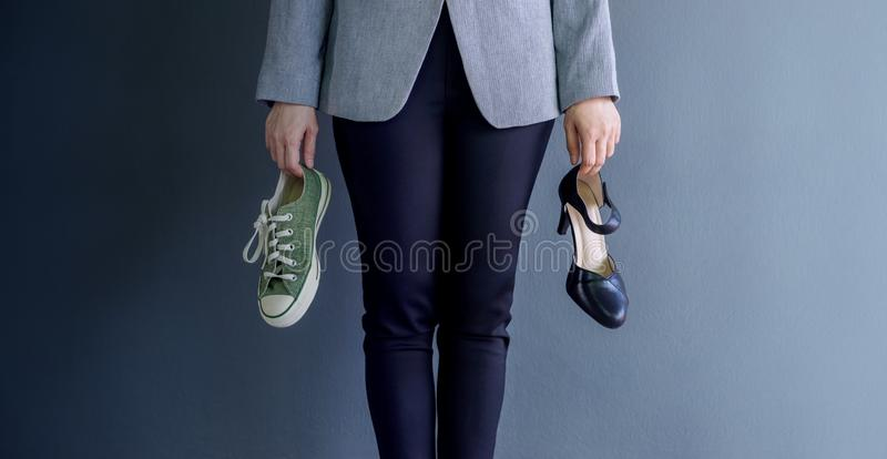 Work Life Balance Concept, present by Business Working Woman holding a High Heal and Sneaker Shoes, Croped image with Copy Space stock photos