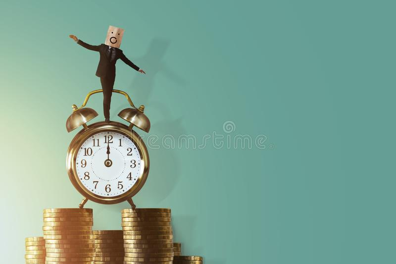 Work Life Balance for Time and Money Concept. Excited Businessman Balancing his body on Vintage Alarm Clock and Stack of Coin. Fa royalty free stock photos