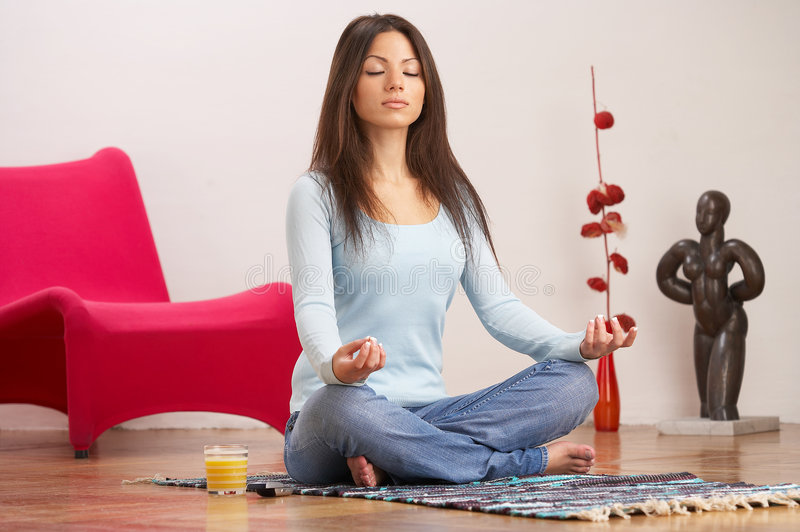Work out. Young lady with long dark brown hair, blue top and jeans, meditating on the floor of her living room royalty free stock image