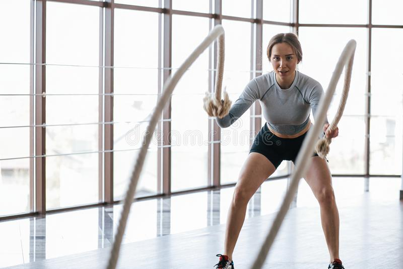 Work out in club near windows. Sportive young woman have fitness day in the gym at morning time stock images