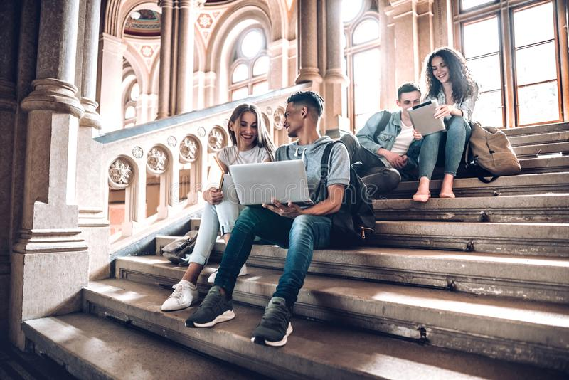 Work with the people that motivate and inspire you.Group of students studying while sitting on stairs in university.  stock image