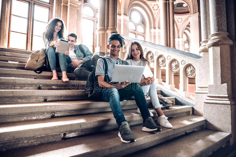 Work with the people that motivate and inspire you.Group of students studying while sitting on stairs in university stock photos