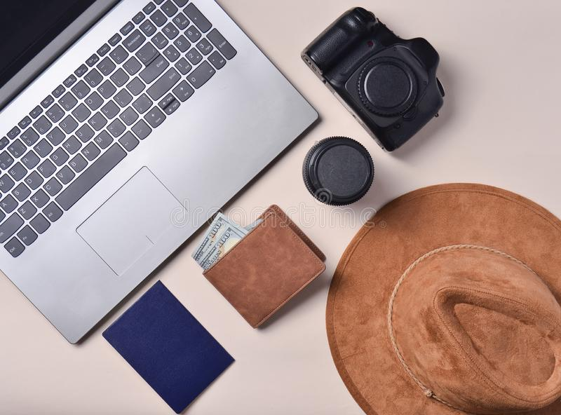 Work of the photojournalist. Laptop, wallet, passport, hat, camera, lens. Travel concept, top view, flat lay. royalty free stock image
