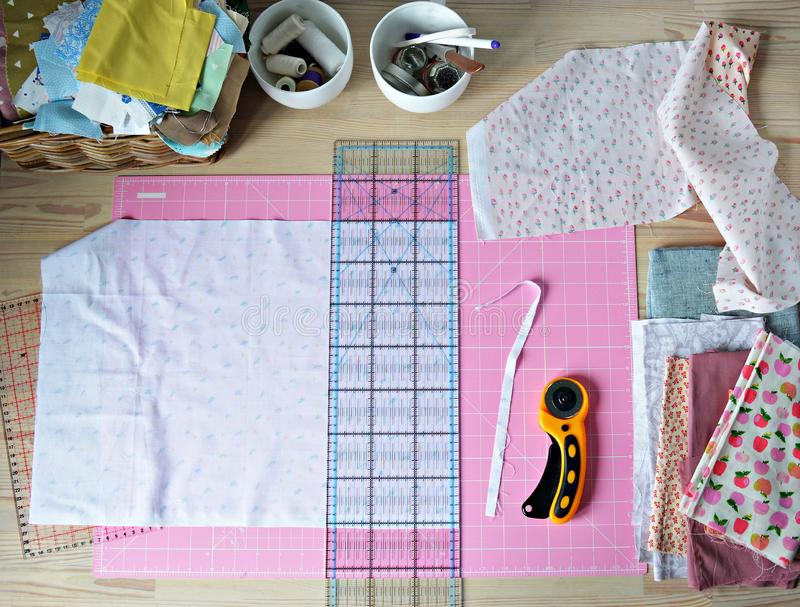 Work place: cotton fabrics, pink cutting mat, quilting ruler, rottary cutter, sewing supplies in white cups. And wooden desk stock photography