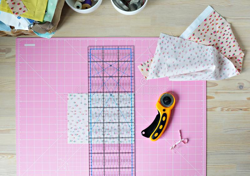 Work place: cotton fabrics, pink cutting mat, quilting ruler, rottary cutter, sewing supplies in white cups. And wooden desk stock photos