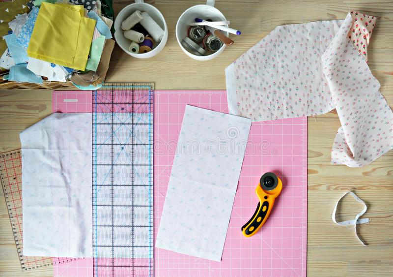 Work place: cotton fabrics, pink cutting mat, quilting ruler, rottary cutter, sewing supplies in white cups. And wooden desk royalty free stock images