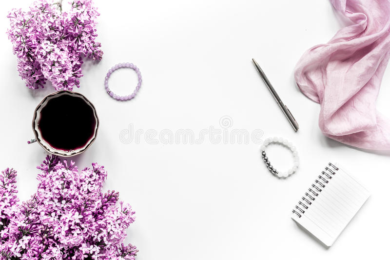 Work place with lilic flowers and coffee for woman on white desk background top view mock-up. Work place with lilic flowers and coffee for woman office on white royalty free stock photography