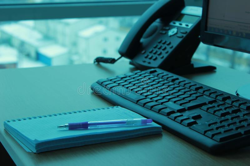 Work place near the window with view on city in fog day. Place in office with computer monitor, keyboard, phone and notebook stock photo