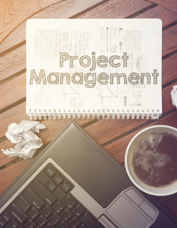Work place - table with notebook with note about: project manage royalty free stock photo