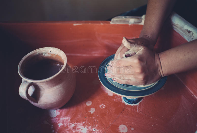 Work in a pottery workshop, womans hands creating ceramics. royalty free stock images