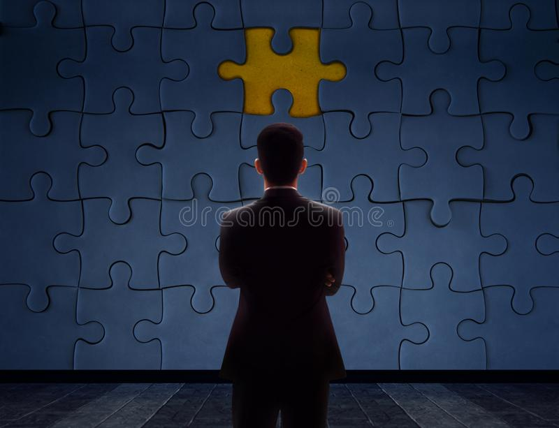 Work Problem Concept. Blurred Back side of a businessman Standing in front of blank Jigsaw Puzzle Wall to Finding a Lost Piece. T royalty free stock photo