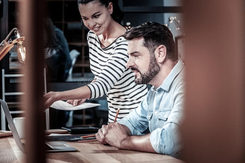 Occupied pleasant employees working with the laptop and smiling. royalty free stock photos