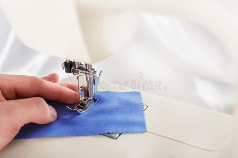 Work in process - sewing machine and hand of tailor with needle, thread and fabric. Item of clothing royalty free stock image