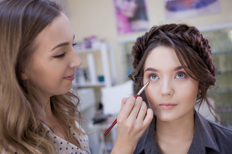 The work of a professional makeup artist. Stylist makeup artist doing makeup and hair in a beauty salon. stock photos