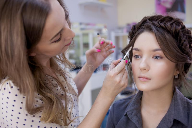 The work of a professional makeup artist. Stylist makeup artist doing makeup and hair in a beauty salon. stock photography