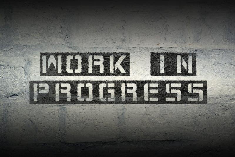 Work in progress gr. Work in progress stencil print on the grunge white brick wall stock photos