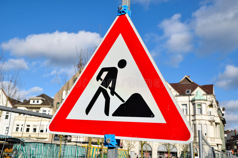 Work in progress road sign triangle isolated on cloudy background. Work in progress road sign isolated on cloudy background in germany royalty free stock photography