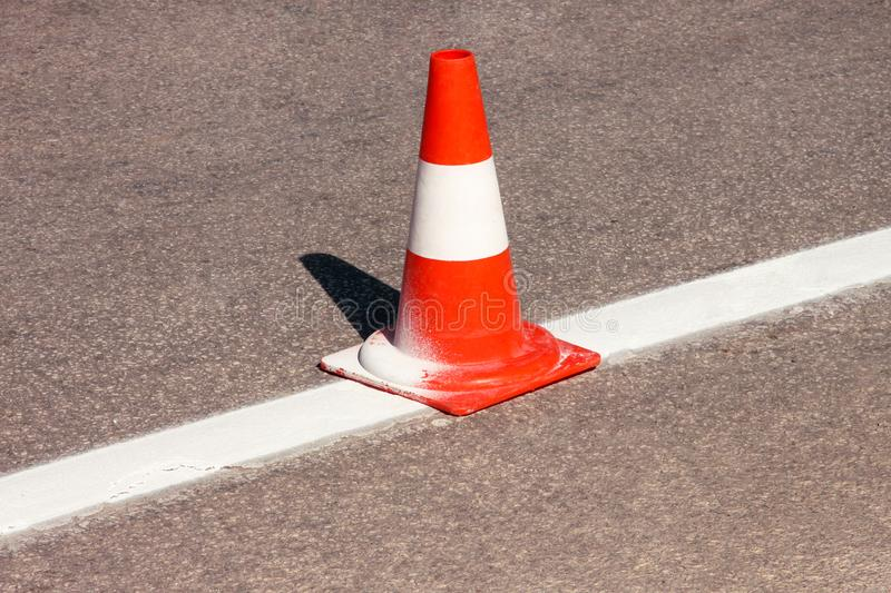 Work on road. Construction cone. Traffic cone, with white and orange stripes on asphalt. Street and traffic signs for signaling. Road maintenance, under stock photography