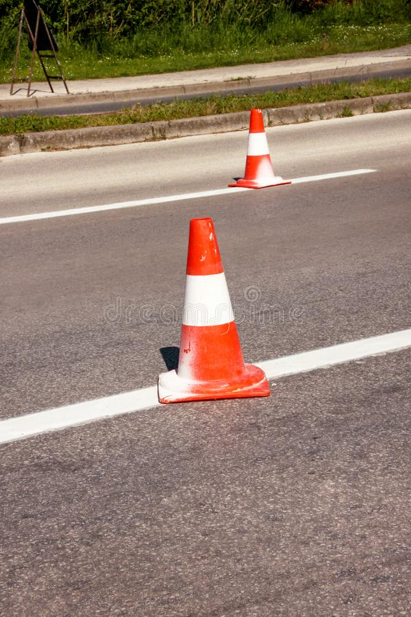 Work on road. Construction cones. Traffic cone, with white and orange stripes on asphalt. Street and traffic signs for signaling. royalty free stock photography