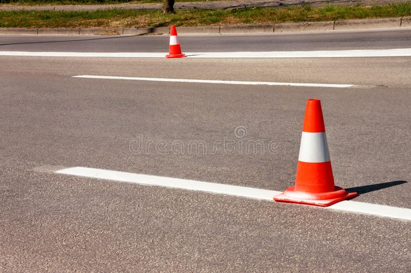 Work on road. Construction cones. Traffic cone, with white and orange stripes on asphalt. Street and traffic signs for signaling. royalty free stock image