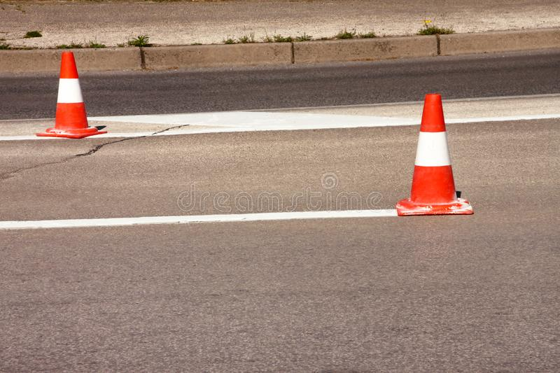 Work on road. Construction cones. Traffic cone, with white and orange stripes on asphalt. Street and traffic signs for signaling. Road maintenance, under royalty free stock photo