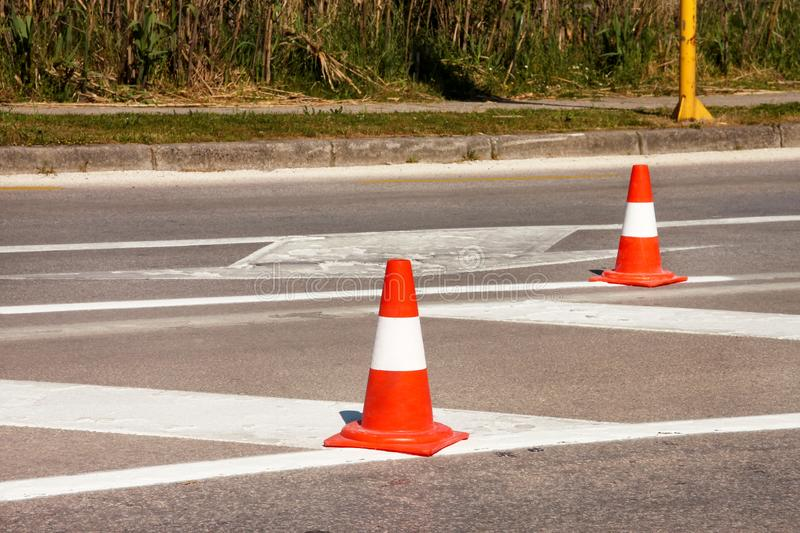 Work on road. Construction cones. Traffic cone, with white and orange stripes on asphalt. Street and traffic signs for signaling. stock photos