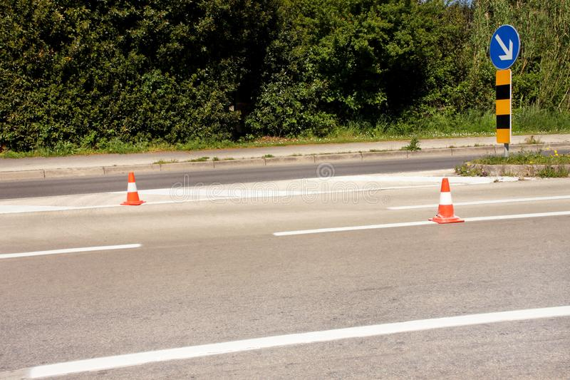 Work on road. Construction cones with traffic sign keep right sign. Traffic cones, with white and orange stripes on asphalt. royalty free stock photo