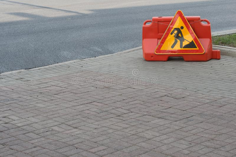 Work on road. Under construction sign. Traffic warning, yellow, orange and red colors. Street and traffic signs for signaling. Work on road. Under construction stock photography