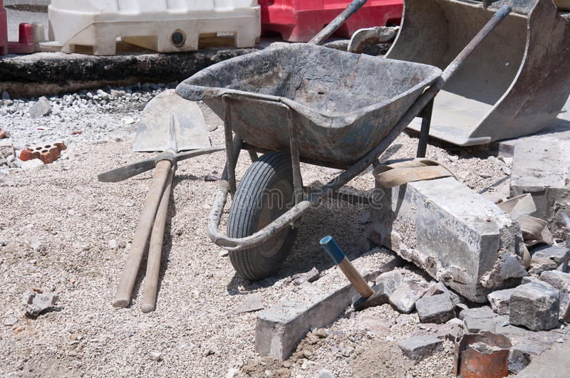 Work on the road with wheelbarrow , a pick and hammer stock images