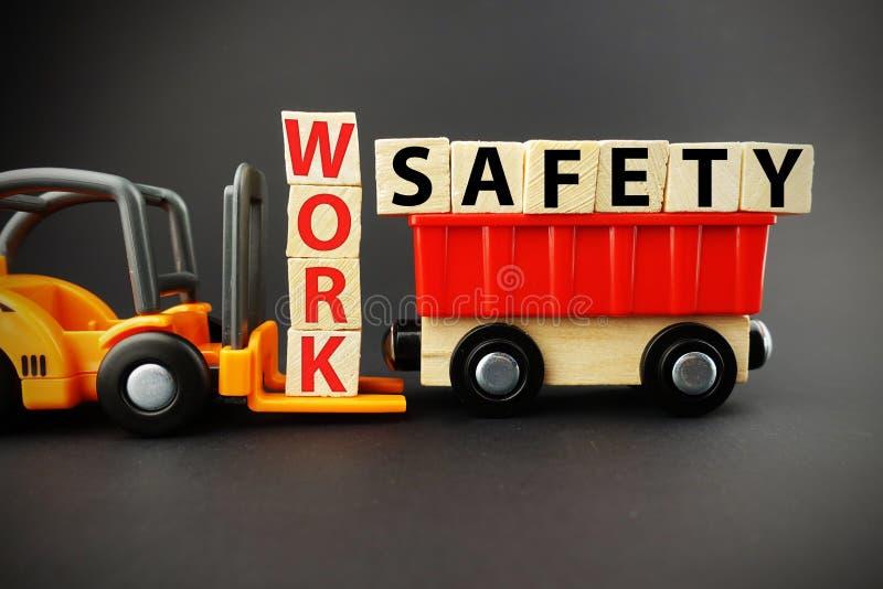 Work safety concept with wooden blocks on orange forklift with dark background stock photo