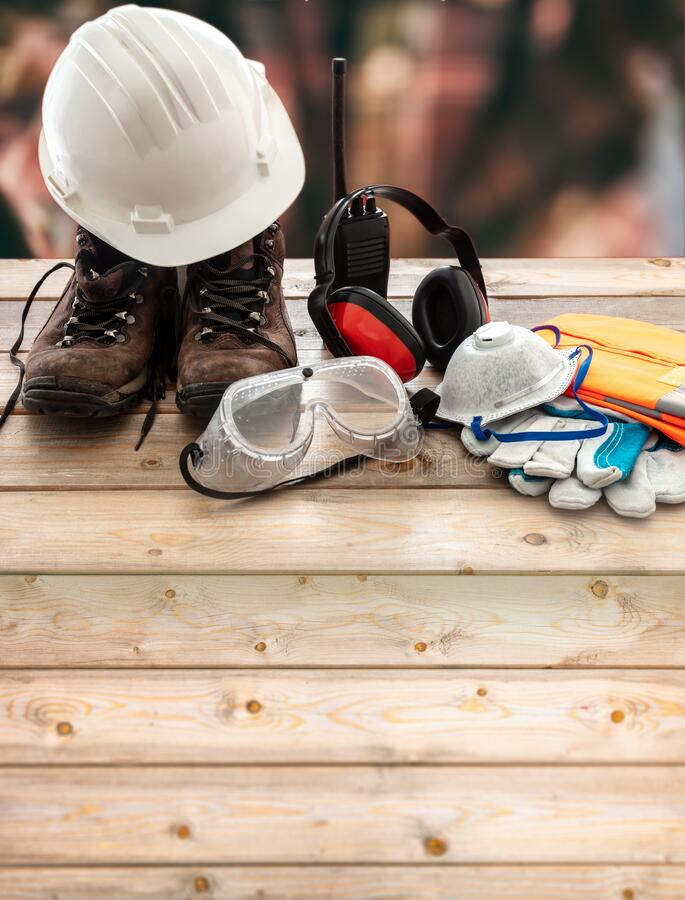 Free Work Safety Protection Equipment. Industrial Protective Gear On Wooden Table, Blur Construction Site Background Royalty Free Stock Photo - 190228275