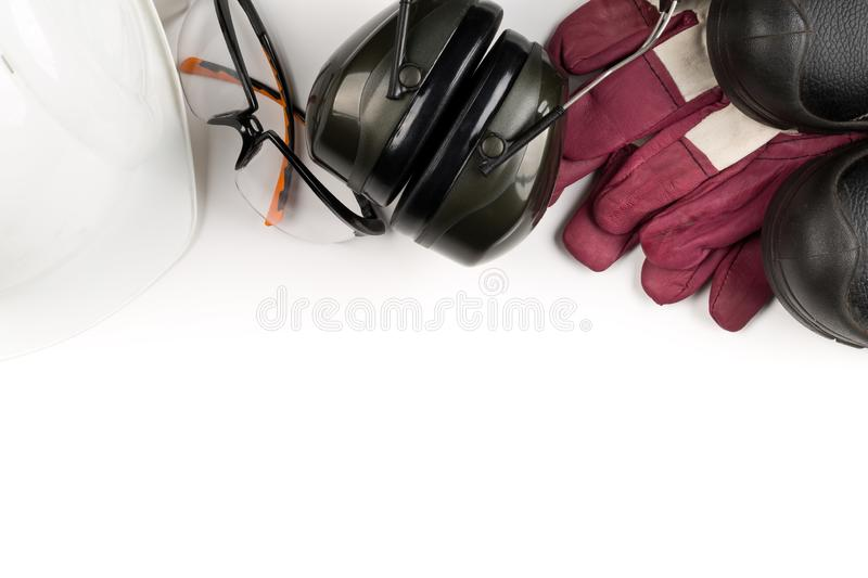 Work safety and protection equipment - protective shoes, safety glasses, gloves and hearing protection. Over white background flat-lay view from above stock image