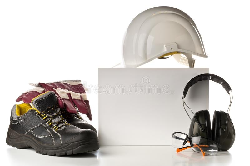 Work safety and protection equipment - protective shoes, safety glasses, gloves and hearing protection. Over white background with blank card for copy royalty free stock image